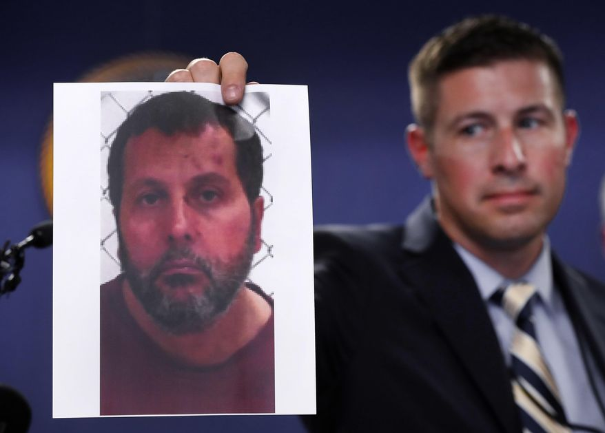 In this file photo, Timothy Wiley, FBI public affairs specialist, holds a photo Amor Ftouhi after a news conference in Detroit, Thursday, June 22, 2017. Amor Ftouhi, a Canadian man, shouted in Arabic before stabbing a police officer in the neck at the Bishop International Airport in Flint, Mich., federal officials said. (AP Photo/Paul Sancya) **FILE**