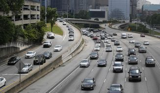 In this Thursday, May 19, 2016, photo, traffic flows out of downtown Atlanta on the Interstate 75/85 Connector, in Atlanta. More people are expected to put down the TV remote and hit the road for the July 4, 2017, weekend. Auto club AAA predicts that 44.2 million people will travel over the holiday period, most of them by car, up 2.9 percent over a year earlier. (AP Photo/John Bazemore)