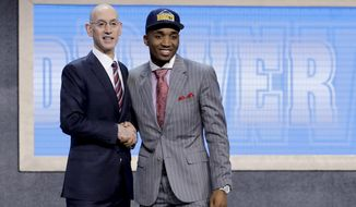Donovan Mitchell poses for photos with NBA Commissioner Adam Silver after being selected by the Denver Nuggets as the 13th pick overall during the NBA basketball draft, Thursday, June 22, 2017, in New York. (AP Photo/Frank Franklin II)