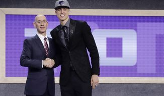 Zach Collins poses for photos with NBA Commissioner Adam silver after being selected by the Sacramento Kings as the 10th pick overall during the NBA basketball draft, Thursday, June 22, 2017, in New York. (AP Photo/Frank Franklin II)
