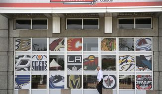 A man pass a United Center entrance with NHL team logos as preparation for the NHL Draft continue, Thursday, June 22, 2017, in Chicago. The two day draft begins Friday. (AP Photo/G-Jun Yam)