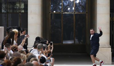 Fashion designer Kim Jones acknowledges applause at the end of Louis Vuitton Men's Spring Summer 2018 fashion collection, presented in Paris France, Thursday, June 22, 2017. (AP Photo/Francois Mori)