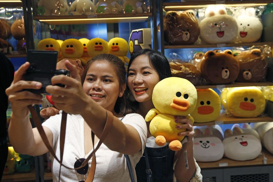 Customers take a selfie with merchandise at Line Village in Bangkok, Thailand, Thursday, June 22, 2017. Thailand's most popular text-messaging service will open its doors to the public Friday with an extravagant digital theme park called Line Village Bangkok. (AP Photo/Sakchai Lalit)