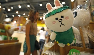 A customer selects merchandise at Line Village in Bangkok, Thailand, Thursday, June 22, 2017. Thailand's most popular text-messaging service will open its doors to the public Friday with an extravagant digital theme park called Line Village Bangkok. (AP Photo/Sakchai Lalit)