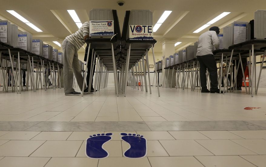 Voters cast ballots at City Hall in San Francisco, Tuesday, Nov. 8, 2016. (AP Photo/Jeff Chiu)