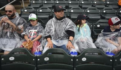 Michael Davis, left, with his son Zeke, from Boise Idaho, and Christopher Veaver with his Daughter, Jaela and Jaguar from Spearfish South Dakota, all first timers to Target Field, wait in the rain for the stop so they can watch a Minnesota Twins and Chicago White Sox baseball game, Thursday, June 22, 2016, in Minneapolis. (AP Photo/John Autey)