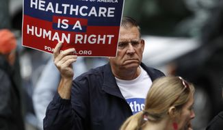 A protester waves a placard during a rally, Friday, June 23, 2017, in downtown Denver, against the Republican health bill that was recently unveiled in the U.S. Senate. More than 100 protesters crowded the sidewalk outside the building in which U.S. Sen. Cory Gardner, R-Colo., has his office. (AP Photo/David Zalubowski)
