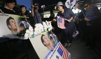 "A woman prays during a memorial rally for the late American student Otto Warmbier near the U.S. Embassy in Seoul, South Korea, Friday, June 23, 2017. North Korea on Friday called itself the ""biggest victim"" in the death of Warmbier who was detained for more than a year and died days after being released in a coma. (AP Photo/Ahn Young-joon)"