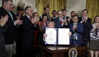 """President Donald Trump displays the """"Department of Veterans Affairs Accountability and Whistleblower Protection Act of 2017"""" after signing in the East Room of the White House, Friday, June 23, 2017, in Washington, as Secretary of Veteran Affairs David Shulkin and others look on. (AP Photo/Evan Vucci)"""