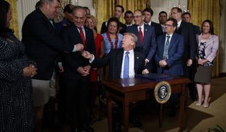 """President Donald Trump hands a pen to Michael Verardo, who lost his leg in Afghanistan serving as a Sergeant in the 82nd Airborne Division in 2010, after signing the """"Department of Veterans Affairs Accountability and Whistleblower Protection Act of 2017"""" in the East Room of the White House, Friday, June 23, 2017, in Washington. (AP Photo/Evan Vucci)"""