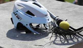 In a photo from April 26, 2017, a lacrosse helmet is displayed at the Cranbrook Kingswood School in Bloomfield Hills, Mich. Helmets are not a required piece of equipment worn by female high school lacrosse players. And this year, the National Federation of State High School Associations allowed the optional use of two models of headgear beyond the previously allowed padded headbands. In 2018, Florida will become the first state to mandate high school female lacrosse players wear protective equipment over their entire head. (AP Photo/Carlos Osorio)