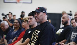 LaVar Ball, center, father of Los Angeles Lakers draft pick Lonzo Ball, listens to his son during the NBA basketball team's news conference, Friday, June 23, 2017, in El Segundo, Calif. (AP Photo/Jae C. Hong) **FILE**