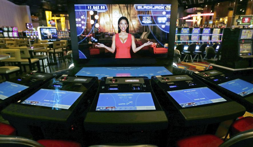 FILE - In this June 23, 2015, file photograph, an automated dealer asks for players to take a seat at a black jack video slot machine on the floor of the Plainridge Park Casino in Plainville, Mass. The state's only casino generated about $157 million in gross gambling revenues since June 2016, slightly higher than the $154 million it registered in its first full year but still far short of the $300 million initially projected for the slots parlor and harness racing track when it opened. (AP Photo/Charles Krupa, File)