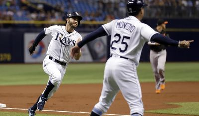 Tampa Bay Rays' Evan Longoria, left, races past third base coach Charlie Montoyo (25) to score on a triple by Logan Morrison off Baltimore Orioles starting pitcher Ubaldo Jimenez during the first inning of a baseball game Friday, June 23, 2017, in St. Petersburg, Fla. (AP Photo/Chris O'Meara)