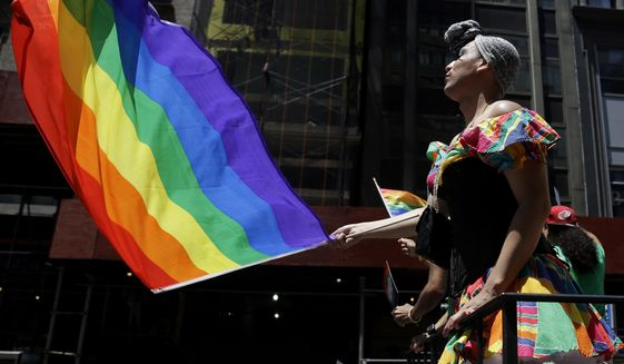 In this June 24, 2014, file photo, people on a float dance and wave flags during the annual pride parade in New York. The annual pride parade takes place on Sunday, June 25, 2017, amid protests by black and brown LGBT people saying increasingly corporate pride celebrations prioritize the experiences of gay white men and ignore the issues continuing to face black and brown LGBT people. (AP Photo/Seth Wenig, File)