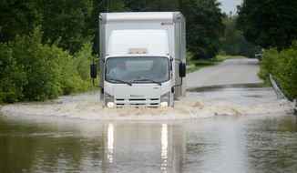 A box truck traverses a flooded portion of North Union Road between Seven Mile Road and Fraser Road in Bay County, Mich., on Friday, June 23, 2017. (Jacob Hamilton/The Bay City Times via AP)