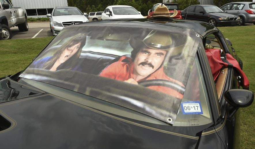 """In this  June 20, 2017 photo, a Pontiac Trans-Am is parked with a cut out photo of actors Burt Reynolds and Sally Field during the 10th Bandit Run in Birmingham, Ala.  The Bandit Run is a reenactment of the journey portrayed in the 1977 movie """"Smokey and the Bandit.""""  (Joe Songer/AL.com via AP)"""