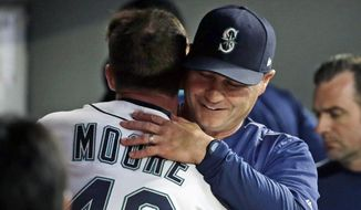 Seattle Mariners manager Scott Servais embraces starting pitcher Andrew Moore in the dugout after Moore finished throwing in the top of the seventh inning of the team's baseball game against the Detroit Tigers on Thursday, June 22, 2017, in Seattle. (AP Photo/Elaine Thompson)