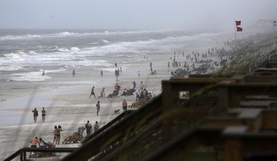 Beachgoers enter the water even though double-red flags are flying, warning of dangerous conditions and extremely rough surf in the remnants of Tropical Storm Cindy, in Seaside, Fla. (AP Photo/Kiichiro Sato)
