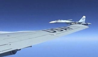 This is a dramatic photo of a Russian jet coming within a few feet of a U.S. Air Force reconnaissance jet over the Baltic Sea on June 19, 2017, in a maneuver that has been criticized as unsafe. The photographs released Friday june 23, 2017, show the Russian SU-27 coming so close to the wing of the U.S. RC-135U. (Master Sgt Charles Larkin Snr/U.S. European Command via AP) ** FILE **