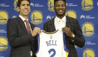 Golden State Warriors NBA basketball draft pick Jordan Bell, right, and general manager Bob Myers pose for photos with a jersey at a news conference in Oakland, Calif., Friday, June 23, 2017. (AP Photo/Jeff Chiu)