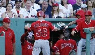 Los Angeles Angels' Kole Calhoun (56) celebrates after scoring on a single by Martin Maldonado during the first inning of a baseball game against the Boston Red Sox, Saturday, June 24, 2017, in Boston. (AP Photo/Michael Dwyer)