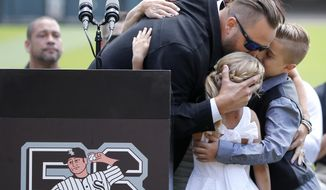 Former Chicago White Sox pitcher Mark Buehrle, left, is hugged by his family, wife Jamie, top, daughter Brooklyn, and son Braden after his No. 56 was retired during ceremonies before a baseball game between the White Sox and the Oakland Athletics Saturday, June 24, 2017, in Chicago. (AP Photo/Charles Rex Arbogast)