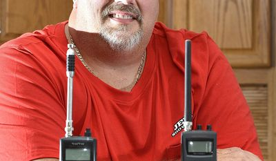 ADVANCE FOR SATURDAY, JUNE 24, 2017 - In this June 16, 2017 photo, Jeff Wessendorf, a long time listener of police radio dispatches poses at his South Sioux City, Neb., home with two of his now-antiquated police radio scanners. Almost all law-enforcement radio traffic on the Siouxland Tri-State Area Radio Communications system - which is used by officers in Sioux City, Woodbury County, North Sioux City, South Sioux City and Dakota County - has been encrypted, leaving police radio scanners silent. (Tim Hynds/Sioux City Journal via AP)