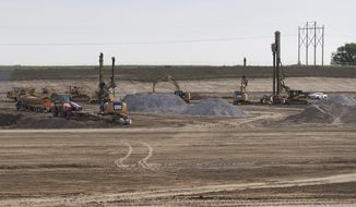 In this Friday, June 16, 2017 photo, equipment drives steel pillars into the ground for where building one will be constructed at a Facebook data center, in Papillion, Neb. (Ryan Soderlin/Omaha World-Herald via AP)