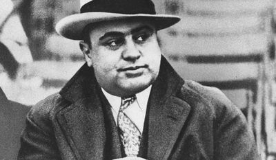 """FILE - In this Jan. 19, 1931 file photograph, Chicago mobster Al Capone is seen at a football game in Chicago. Artifacts connected to some of the nation's most notorious gangsters are being auctioned this weekend. A handwritten musical composition by Al Capone, a letter written by a jailed John Gotti asking someone to """"keep the martinis cold,"""" and jewelry that belonged to Bonnie and Clyde are among the items up for bid Saturday in the """"Gangsters, Outlaws and Lawmen"""" auction in Cambridge, Mass. (AP Photo/File)"""