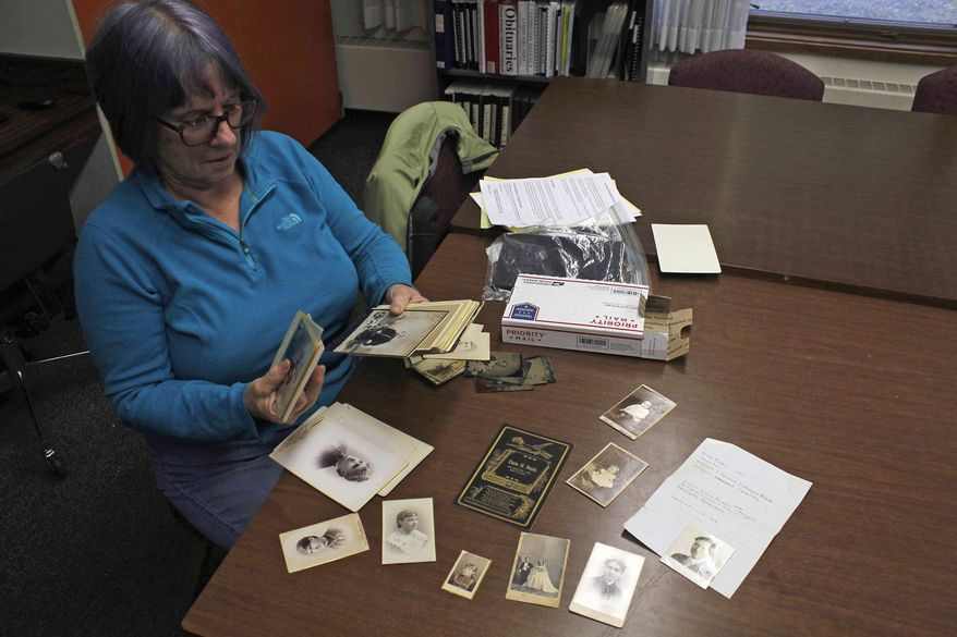 ADVANCE FOR WEEKEND JUNE 24-25, 2017 AND THEREAFTER - In this June 12, 2017 photo, Carol Bruce of the Gastineau Genealogical Society, looks through photos that were anonymously donated to the Friends of the Juneau Public Library in Juneau, Alaska. Some of the photos date back to the 19th Century, and the GGS is trying to find their rightful owners. (Alex McCarthy/Juneau Empire via AP)