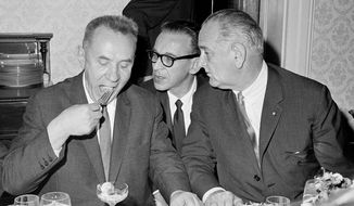 FILE - In this June 23, 1967 file photo, Soviet Premier Alexi Kosygin takes a bite of shrimp cocktail as State Department Interpreter, Bill Kramer, center, relays the words of President Lyndon Johnson, right, during a luncheon meeting of the leaders on the Glassboro State College campus in Glassboro, N.J. Fifty years ago during the Cold War, Johnson and Kosygin decided to talk as the Six-Day War raged in the Mideast. They settled on a place halfway between New York and Washington and selected the school to host the hastily arranged summit in the college president's mansion. (AP Photo/Jerry Mosey, File)