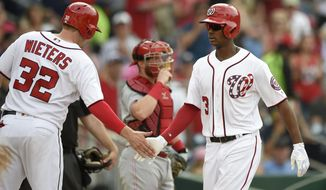 Washington Nationals' Michael Taylor (3) is greeted by Matt Wieters (32) after he hit a two-run home run during the fourth inning of a baseball game as Cincinnati Reds catcher Tucker Barnhart, center, watches Saturday, June 24, 2017, in Washington. (AP Photo/Nick Wass)