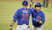 Chicago Cubs' Miguel Montero, right, high-fives first base coach Brandon Hyde (16) after hitting single during the seventh inning of a baseball game against the Miami Marlins, Sunday, June 25, 2017, in Miami. The Marlins won 4-2. (AP Photo/Lynne Sladky)