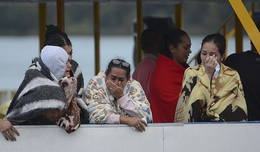 People cry as they wait for more information on tourists who were on a ferry that sank in a reservoir in Guatape, Colombia, Sunday, June 25, 2017. Nine people were dead and 28 missing after a tourist ferry packed with around 170 passengers for the holiday weekend capsized Sunday on a reservoir near the Colombian city of Medellin, officials said. (AP Photo/Luis Benavides)