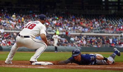 Milwaukee Brewers' Eric Sogard, right, dives back to first as Atlanta Braves first baseman Matt Adams (18) tries to pick him off during the third inning of a baseball game, Sunday, June 25, 2017, in Atlanta, Ga. (AP Photo/Butch Dill)