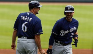 Milwaukee Brewers third baseman Travis Shaw (21) celebrates with third base coach Ed Sedar (6) after hitting a two-run home run against the Atlanta Braves during the first inning of a baseball game, Sunday, June 25, 2017, in Atlanta, Ga. (AP Photo/Butch Dill)