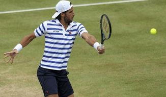 Spain's Feliciano Lopez returns a ball to Croatia's Marin Cilic during their final match at The Queen's Club tennis tournament in London, Sunday June 25, 2017. (Steven Paston/PA via AP)