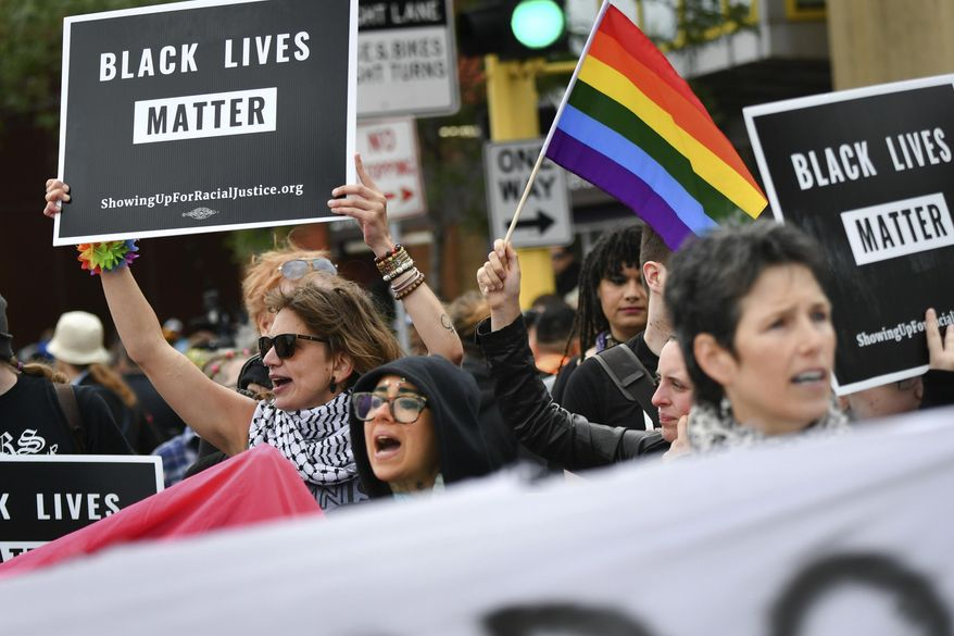 Black Lives Matter protesters block the Twin Cities Pride Parade along Hennepin Ave at the start of the parade in Minneapolis, Sunday, June 25, 2017.  Sunday's parade was disrupted over the police shooting of Philando Castile just minutes after getting underway in downtown Minneapolis.  (Glen Stubbe/Star Tribune via AP)