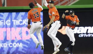 Miami Marlins left fielder Marcell Ozuna (13), right fielder Giancarlo Stanton, center, and center fielder Ichiro Suzuki celebrate after defeating the Chicago Cubs in a baseball game, Sunday, June 25, 2017, in Miami. (AP Photo/Lynne Sladky)