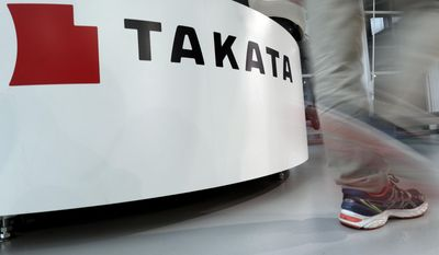 In this May 10, 2017 photo, a visitor walks past the logo of Takata Corp. at a Toyota showroom in Tokyo. Japanese air bag maker Takata Corp. filed for bankruptcy protection in Tokyo on Monday, June 26, 2017 and the U.S., drowned in a sea of lawsuits and recall costs. (AP Photo/Shizuo Kambayashi)