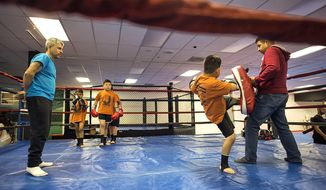 ADVANCE FOR WEEKEND EDITIONS, JUNE 24-25 - In this recent photo, youngsters work out at  NorthWest Combat Fitness at the Three Rivers Mall in Kelso, Wash. Brittany Marquez is not a mixed martial arts fighter and only recently started to appreciate the sport, so she surprised even herself by opening an MMA studio. (Bill Wagner/The Daily News via AP)