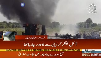 In this image taken from video, black smoke rises from oil tanker on road in Bahawalpur, Pakistan, Sunday,  June 25, 2017.  An overturned oil tanker burst into flames in Pakistan on Sunday, killing people who had rushed to the scene of the highway accident to gather leaking fuel, an official said. (AAJ News via AP Video)