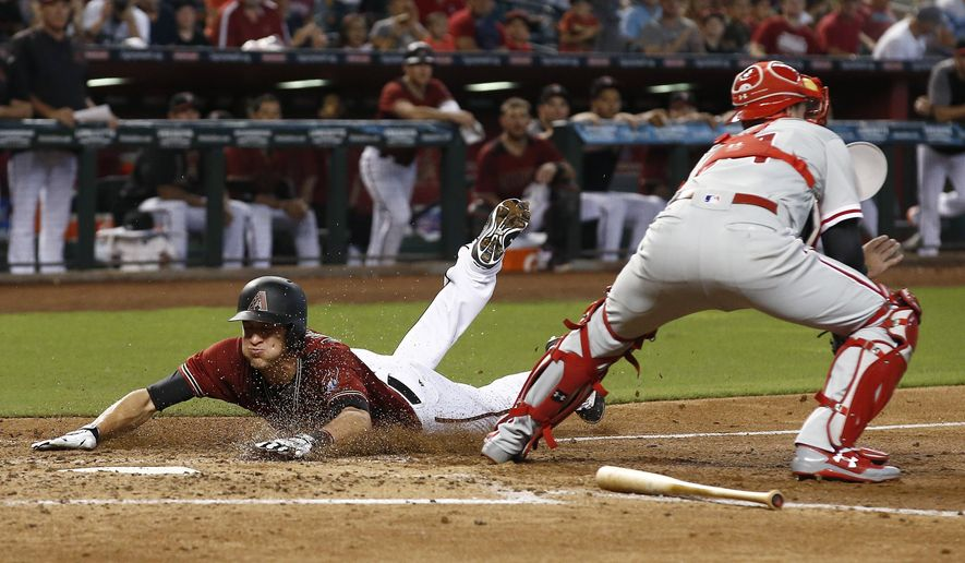 Arizona Diamondbacks' Nick Ahmed, left, scores a run as Philadelphia Phillies' Andrew Knapp, right, makes a catch on a late throw to home plate during the fourth inning of a baseball game Sunday, June 25, 2017, in Phoenix. (AP Photo/Ross D. Franklin)