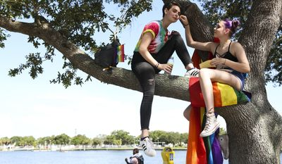 From left, Emma Chalut gets a rainbow sticker on her cheek from her sister Ellie before the gay pride parade in St. Petersburg, Fla., Saturday, June 24, 2017. (Eve Edelheit/Tampa Bay Times via AP)