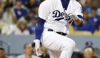 Los Angeles Dodgers' Yasmani Grandal watches his RBI single against the Colorado Rockies during the third inning of a baseball game in Los Angeles, Saturday, June 24, 2017. (AP Photo/Chris Carlson)