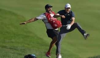 Jordan Spieth, right, celebrates with caddie Michael Greller after Spieth holed a bunker shot on a playoff hole on the 18th hole to win the Travelers Championship golf tournament Sunday, June 25, 2017, in Cromwell, Conn.  (Brad Horrigan/Hartford Courant via AP)