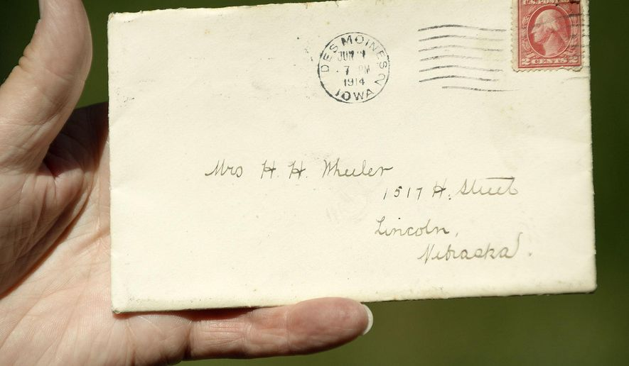 In this Thursday, June 15, 2017 photo, a letter, addressed to Mrs. H.H. Wheeler and postmarked in Des Moines in 1914, showed up in letter carrier Larry Schultz' batch of mail to deliver Thursday in Lincoln, Neb. Problem is: Grace Wheeler died in 1947, and her family home came tumbling down in 1965 to make way for the Nebraska Capitol's south parking lot. (Eric Gregory/The Journal-Star via AP)