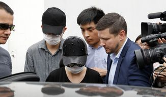 Unidentified Crown Resorts employees wearing face masks are escorted by securities as they leave the Baoshan District People's Court after attending her trial in Shanghai, China, Monday, June 26, 2017. Australian and Chinese employees of a casino company on Monday pleaded guilty to charges relating to gambling and the three Australians were sentenced to nine or 10 months' imprisonment, an Australian official said. (AP Photo/Andy Wong)