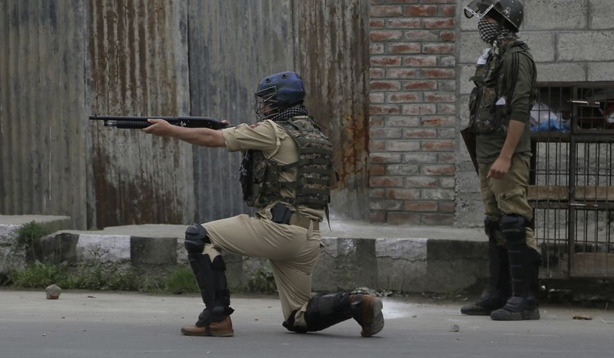 An Indian paramilitary force soldier fires a pellet gun during a protest after Eid al-Fitr prayers in Srinagar, Indian controlled Kashmir, Monday, June 26, 2017. Indian forces used tear gas and pellet guns to disperse hundreds of stone-throwing protesters who took to the streets after Eid al-Fitr prayers protesting Indian rule on Monday. (AP Photo/Mukhtar Khan)